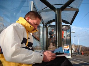 man sitting in bus shelter