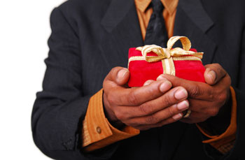 red box bound in gold ribbon being held in a pair of hands